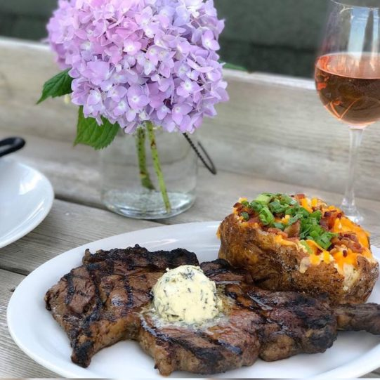 Steak, loaded baked potato, and a glass of wine - with a view at Cowfish.